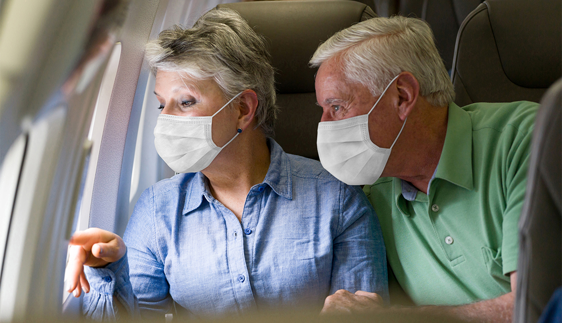 Senior couple traveling by plane wearing facemasks